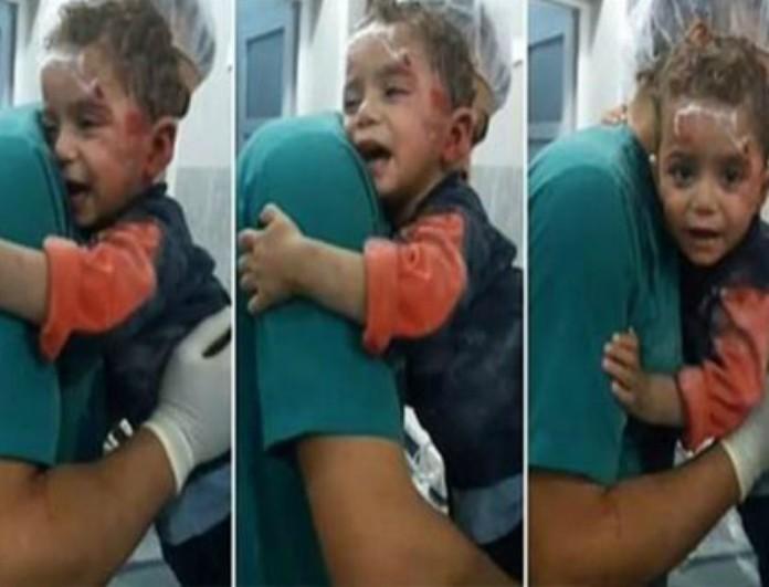 H τραγική στιγμή που ένα αιματοβαμμένο αγοράκι αρνείται να αφήσει τον νοσοκόμο όταν το σπίτι του χτυπήθηκε από μια αεροπορική επιδρομή!