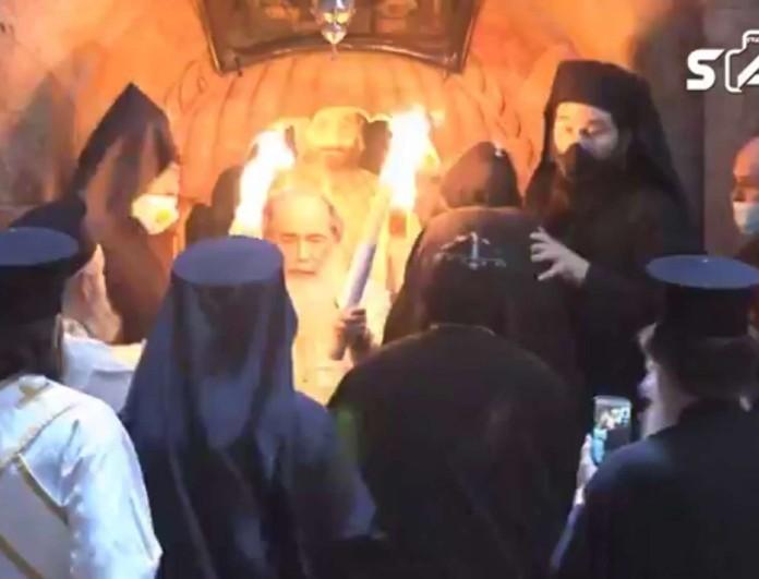 Συγκλονίζει η εικόνα από τον Πανάγιο Τάφο - Ιερείς με μάσκες πάνω από το Άγιο Φως